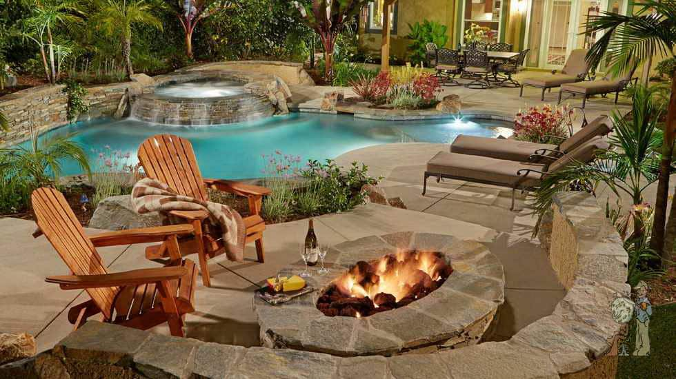 freeform pool with stacked stone spa and lounge chairs by firepit