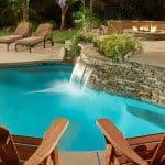 stacked stone custom swimming pool with waterfall and lounge chairs