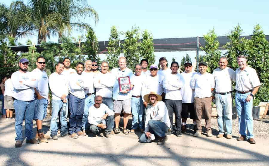 Landscape Construction and Design crew posing with award for best unlimited install