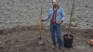 Ian holding a shovel and the 15 gallon Fuyu Persimmon