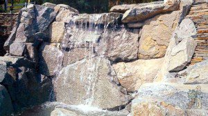 boulders skillfully cut and placed to form waterfall