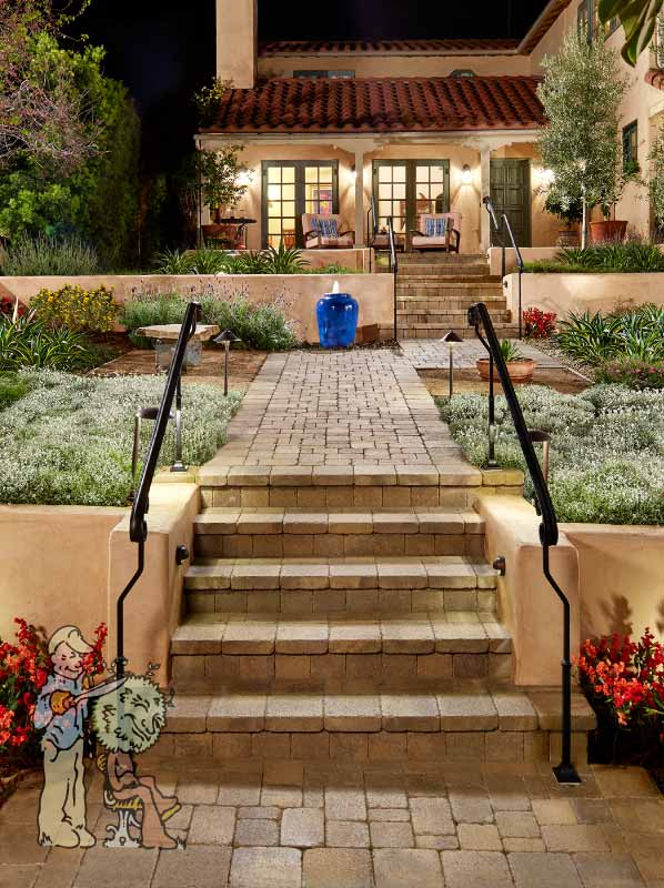 paver entry path to Spanish style house with blue pot fountain