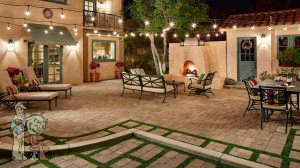 Spanish style backyard fireplace with pavers and hanging lights