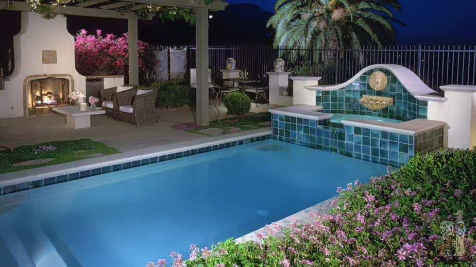 Formal swimming pool with fountain into spa, fireplace, arbor, and seating area in Altadena