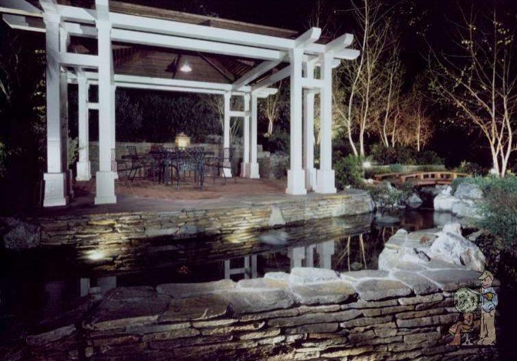 Arbor at night above stone koi pond