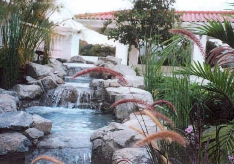 Azusa Grey rock stream waterfall leading away from Mediterannean style house