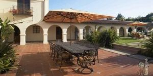 mediterranean tiled patio with table and umbrella