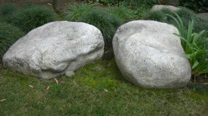 mondo grass plantings accentuating two river rock boulders in grass law