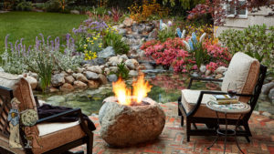 carved boulder firepit over brick deck overlooking pond waterfall