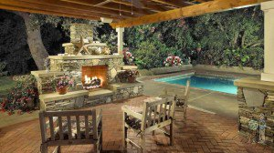 outdoor fireplace by pool with brick pavers