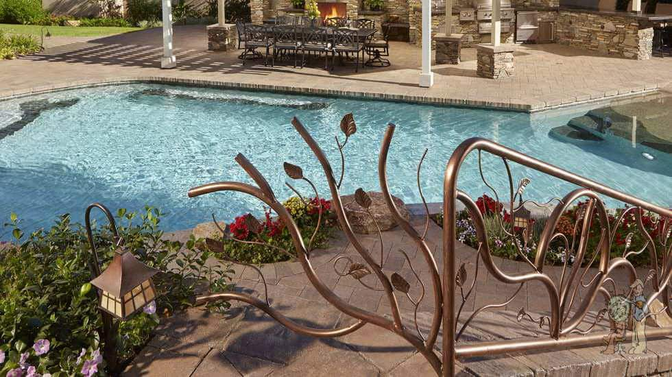 Custom wrought iron railing by swimming pool and outdoor kitchen