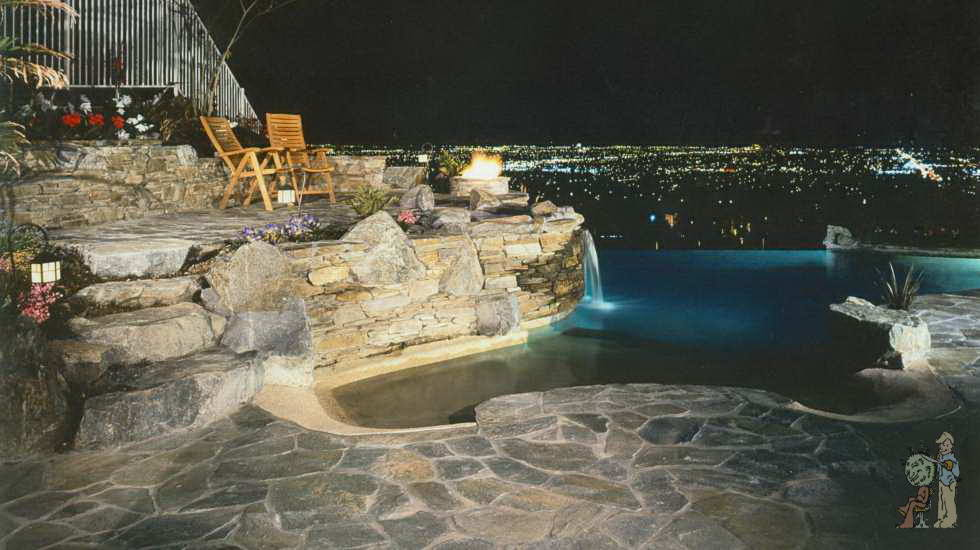 Night time city view from Custom rock infinity pool with seating area
