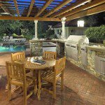 Outdoor dining room and kitchen under wood pergola with bbq