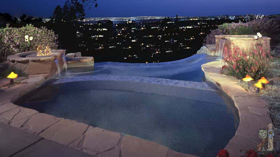 Infinity dunking pool with spa and firepit at night in Kinneloa Canyon