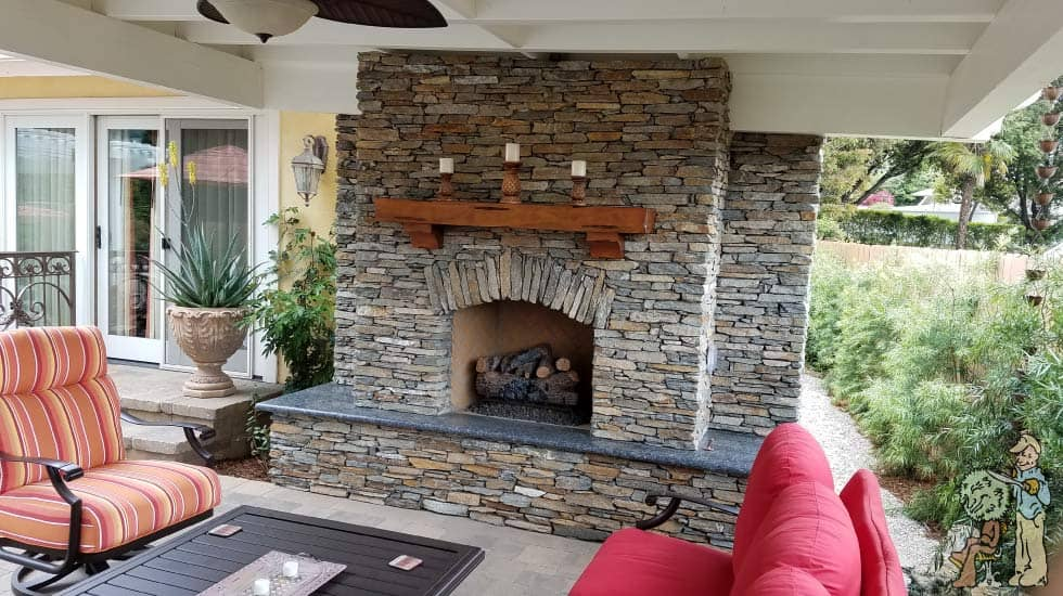 outdoor stacked stone fireplace with candles and bamboo landscape