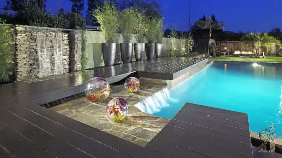 Swimming Pool with waterfall streaming into pool under custom wood deck