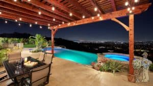 trellis overhang looking over night sky and inifnity edge pool