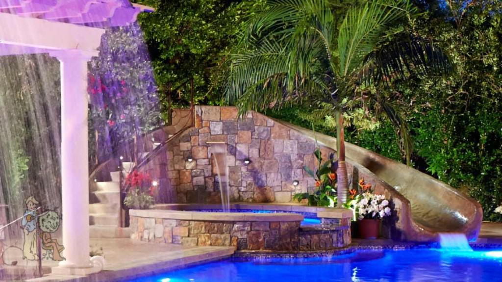 free form pool with custom waterslide into fiber optic pool